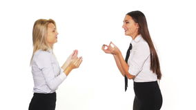 Two businesswomen in a contradiction - studio shot. Two businesswomen in a contradiction a white background stock footage