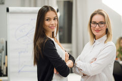 Two businesswomen coworkers standing in an office and smiling positively at the camera while holding folder of paperwork Royalty Free Stock Photography