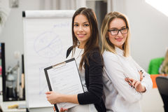 Two businesswomen coworkers standing in an office and smiling positively at the camera while holding folder of paperwork stock photography