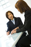 Two businesswomen at desk. Two businesswomen writing and sitting at a desk in a white office royalty free stock photography