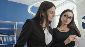 Two businesswomen discusses the contract in the office stock video footage