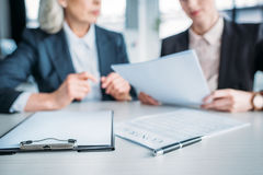 Two businesswomen discussing business project on meeting in office, clipboard and contract on foreground. Cropped view of two businesswomen discussing business Stock Images