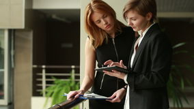 Two businesswomen discussing a contract. go around the office stock footage