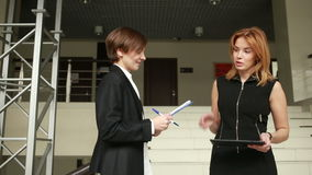 Two businesswomen discussing a contract. go around the office stock video footage