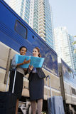 Two businesswomen discussing document on railway platform beside stationary passenger train, low angle view Royalty Free Stock Image