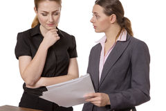 Two Businesswomen Discussing Paperwork. Two Young Professional Businesswomen Discussing Paperwork In The Office Stock Photos