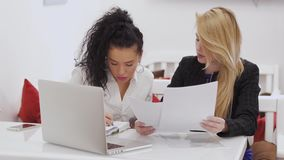 Two businesswomen discussing work issues and looks through the documents in cafe. Two businesswomen sits in cafe and discussing work issues and looks through the stock video footage