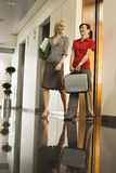 Two businesswomen exiting elevator into office corridor, carrying briefcase, smiling, surface level Royalty Free Stock Photo