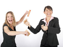 Two businesswomen fighting with rubber stamps Royalty Free Stock Photography