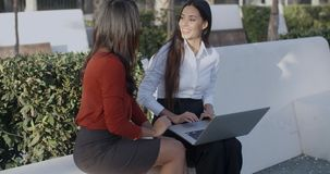 Two businesswomen having an informal meeting. Two attractive stylish businesswomen sitting outdoors in an urban square having an informal meeting chatting stock footage
