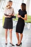 Two Businesswomen Having Informal Meeting In Modern Office. Discussing Stock Photos