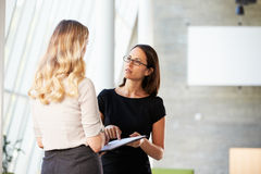 Two Businesswomen Having Informal Meeting In Modern Office. Discussing Royalty Free Stock Photos