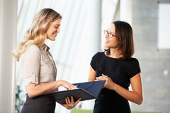 Two Businesswomen Having Informal Meeting In Modern Office royalty free stock photo