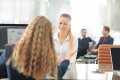 Two Businesswomen Having Informal Meeting In Modern Office. Image of two friendly businesswomen sitting and discussing new ideas Stock Image