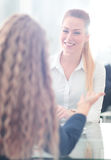 Two Businesswomen Having Informal Meeting In Modern Office. Image of two friendly businesswomen sitting and discussing new ideas Royalty Free Stock Image
