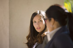 Two businesswomen having meeting outdoors, side view (differential focus) Stock Images