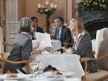 Two Businesswomen Looking At Documents At Restaurant Table. With men in background Royalty Free Stock Photos