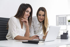 Two businesswomen looking at a laptop screen together Stock Photography