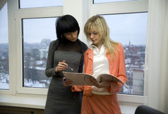 Two businesswomen looking into papers Royalty Free Stock Image