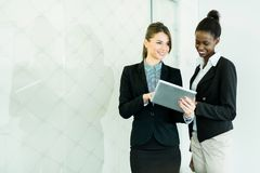 Two businesswomen looking at a tablet with a glass reflection Royalty Free Stock Photography