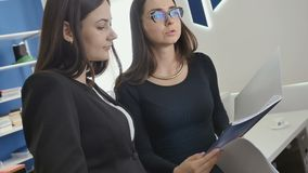 Two businesswomen looks through the documents in the office. Two businesswomen are in the office. Young women has a conversation and discussing the agreement in stock footage