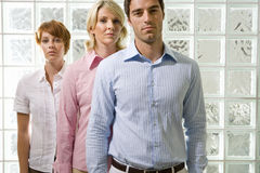 Two businesswomen and man standing in line by glass block wall, portrait stock images