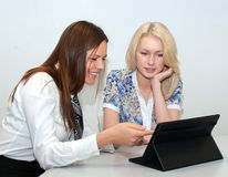 Two Businesswomen Meeting In Office. With tablet pc Royalty Free Stock Image