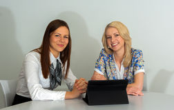 Two Businesswomen Meeting In Office with tablet pc. Smiling Stock Photo
