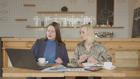Two businesswomen networking with gadgets in cafe. Concentrated on work female business partners sitting at cafe table viewing laptop screen agreeing with stock video