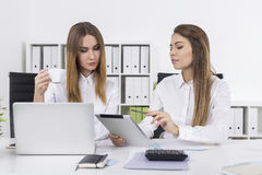 Two businesswomen in office with a cup of coffee Royalty Free Stock Image