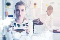 Two businesswomen in office, graphs Stock Photos