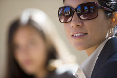 Two businesswomen outdoors, focus on woman wearing sunglasses in foreground, smiling, side view, portrait Royalty Free Stock Photography