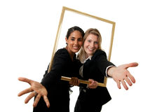 Two businesswomen pictureframe. A young indian and a young european businesswoman stretching their hands through a pictureframe Royalty Free Stock Images