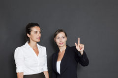 Two businesswomen pointing on a virtual screen Stock Photos