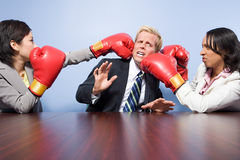 Two businesswomen punching a businessman Royalty Free Stock Images