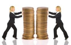 Two businesswomen push rouleau money Royalty Free Stock Photo