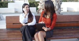 Two businesswomen relaxing in an urban park. Two businesswomen relaxing in an urban sitting together on an outdoor bench  one chatting on a mobile phone watched stock footage