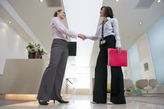 Two businesswomen shaking hands in lobby, smiling, side view, surface level Stock Photography
