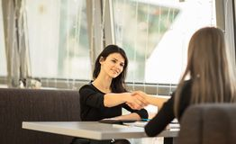 Two Businesswomen Shaking Hands. In Modern Office Royalty Free Stock Photos