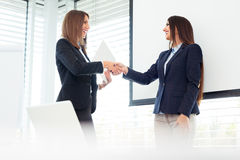 Two Businesswomen Shaking Hands In Modern Office Stock Images