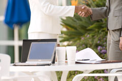 Two businesswomen shaking hands beside pavement cafe table, side view, mid-section Stock Photography