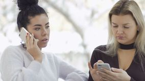 Two attractive businesswomen uses phones. Two businesswomen sits near the window and uses their phones. Pretty brunette talks on phone, her colleague is stock video footage