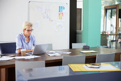Two Businesswomen Sitting At Desks In Office Using Laptops Royalty Free Stock Photo