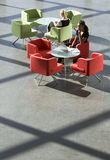 Two businesswomen sitting at tables in an office building Royalty Free Stock Photography