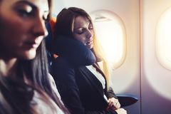 Two businesswomen sleeping in the airplane using neck cushion while going on business trip Stock Photography