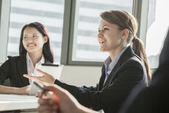 Two businesswomen smiling, discussing, and gesturing during a business meeting Royalty Free Stock Images