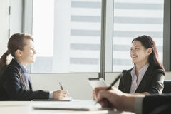 Two businesswomen smiling and looking at each other during a business meeting Stock Photos