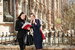 Two businesswomen. Standing on the building background and looking at documents Stock Photography