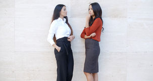 Two businesswomen standing chatting outdoors Royalty Free Stock Images