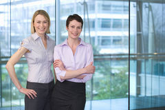 Two businesswomen standing beside large window in office, arm in arm, smiling, portrait Stock Image